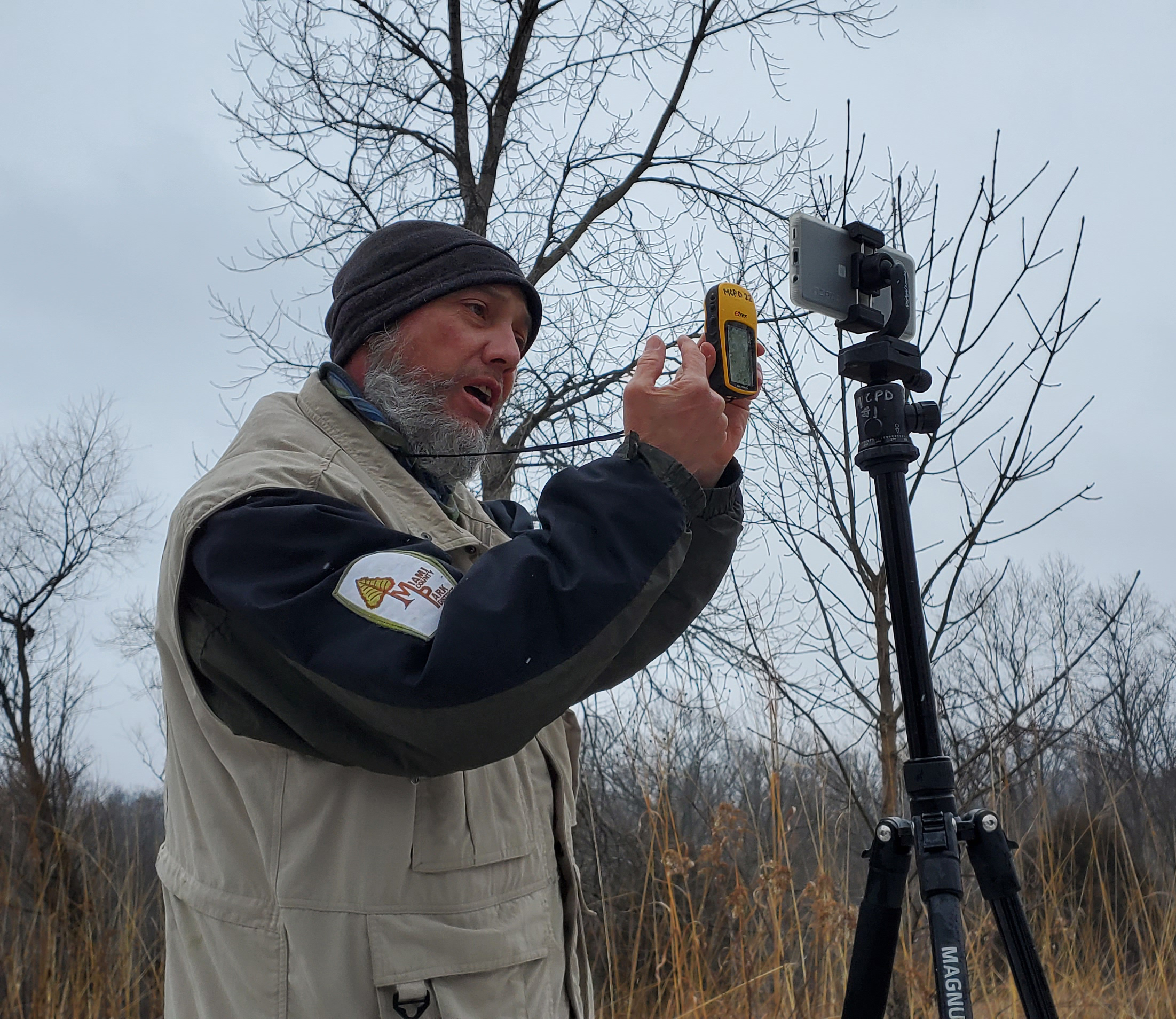 Naturalist holding a GPS unit up to a camera