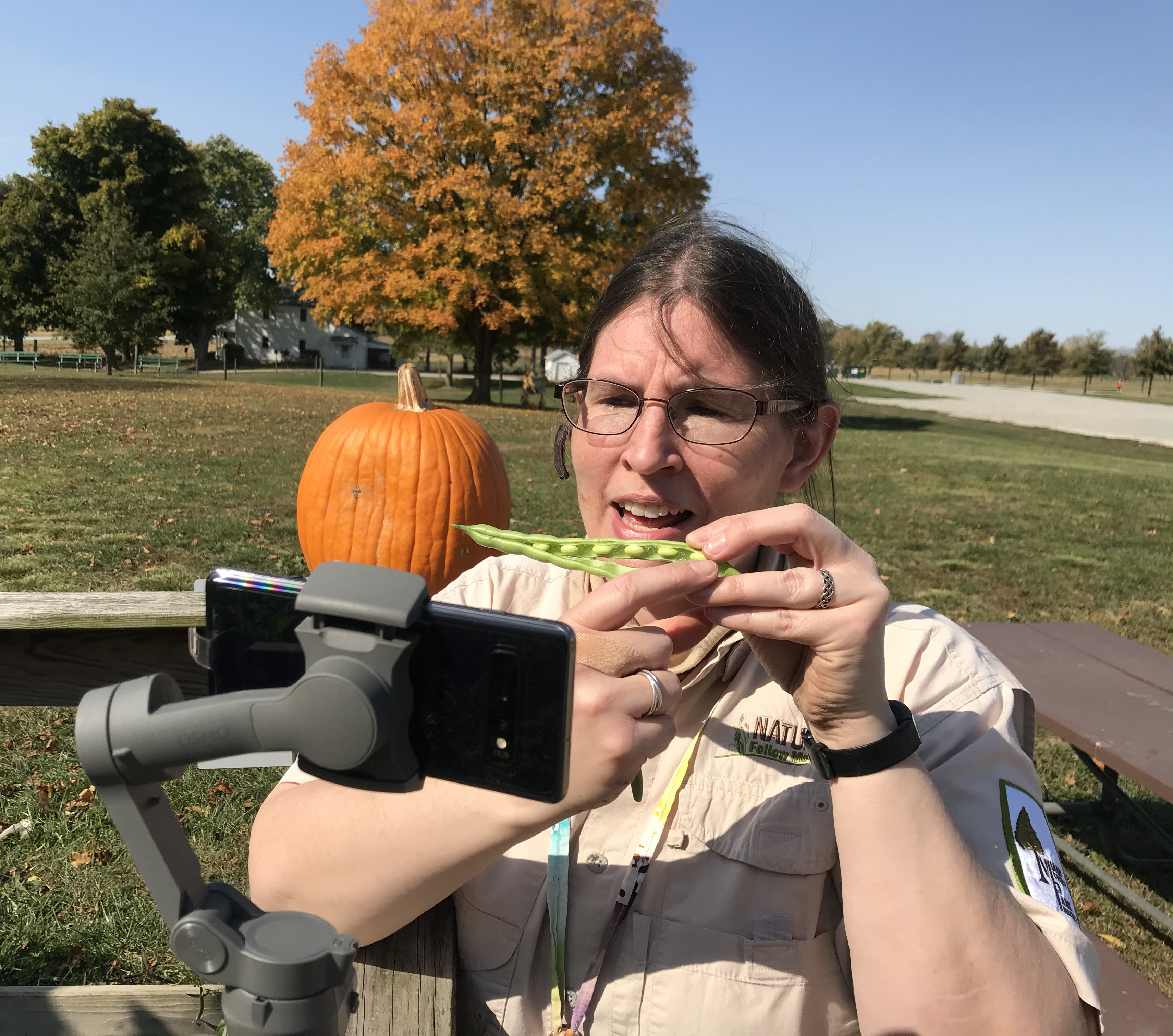 Naturalist showing a pumpkin in front of a camera.
