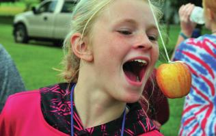 Girl trying to catch apple on string